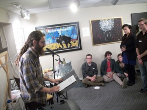 Musician and composer Peter Brewer reads a poem at the Art & Words show reading.